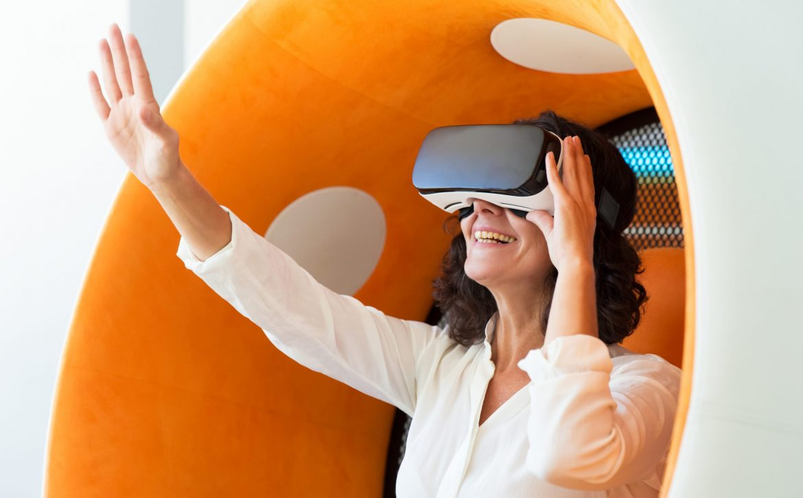 Amazed business woman in VR headset touching air