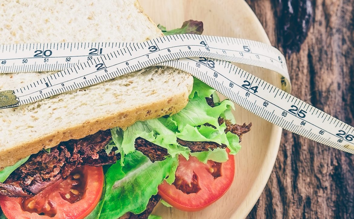 Sandwich with cold soft drink and measurement tape as diet conce